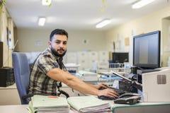 giovane stile dell'uomo dei pantaloni a vita bassa 30s che lavora all'ufficio Fotografie Stock