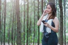 Giovane stile di vita della donna di sport facendo uso dello Smart Phone dopo avere corso Immagine Stock
