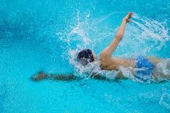 Giovane stile libero maschio di nuoto dell'atleta in stagno Immagine Stock