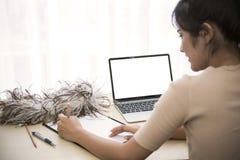 Giovane stilista che lavora per l'indumento della cucitrice in studio immagini stock libere da diritti