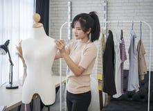 Giovane stilista che lavora per l'indumento della cucitrice in studio fotografia stock