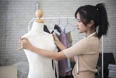 Giovane stilista che lavora per l'indumento della cucitrice in studio fotografie stock