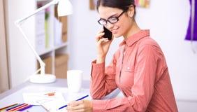 Giovane stilista femminile attraente che lavora alla scrivania, dissipante mentre comunicando sul mobile fotografia stock libera da diritti
