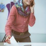 Giovane stilista femminile attraente che lavora alla scrivania, dissipante mentre comunicando sul mobile fotografie stock libere da diritti