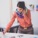 Giovane stilista femminile attraente che lavora alla scrivania, dissipante mentre comunicando sul mobile Immagine Stock