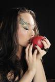 Giovane strega che bacia una mela rossa Fotografia Stock