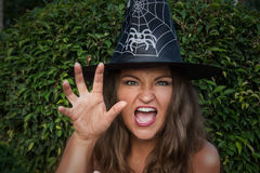 Giovane strega nello spaventare black hat con la sua mano Fotografia Stock Libera da Diritti