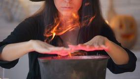 Giovane strega in vestito nero che evoca e che cucina pozione, magia di vigilia di Halloween archivi video