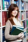 Giovane studente adulto femminile con il libro in biblioteca Fotografie Stock Libere da Diritti