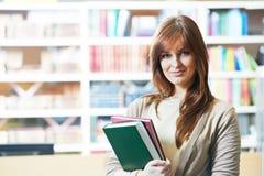 Giovane studente adulto femminile con il libro in biblioteca Immagini Stock Libere da Diritti