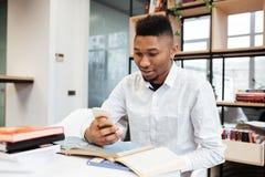 Giovane studente africano in biblioteca che chiacchiera dal suo telefono Immagini Stock
