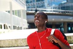 Giovane studente africano felice che si siede all'aperto Immagine Stock