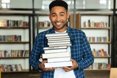 Giovane studente africano felice dell'uomo che sta nella biblioteca Immagine Stock