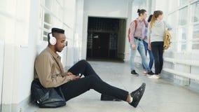 Giovane studente afroamericano bello che si siede sul pavimento in corridoio bianco con le cuffie sulla testa che ascolta la musi video d archivio