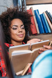 Giovane studente afroamericano che studia con i libri ed i manuali Fotografie Stock