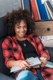 Giovane studente afroamericano che studia con i libri ed i manuali Fotografie Stock Libere da Diritti