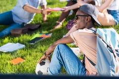Giovane studente afroamericano con pallone da calcio che si siede sull'erba mentre compagni di classe che studiano dietro nel par Fotografia Stock Libera da Diritti
