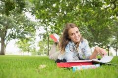 Giovane studente allegro che studia sull'erba Fotografie Stock
