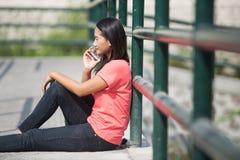 Giovane studente asiatico all'aperto, parlando sul telefono mentre sedendosi Fotografie Stock