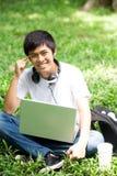 Giovane studente asiatico bello con il computer portatile ed il sorriso in all'aperto immagine stock libera da diritti