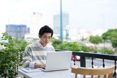 Giovane studente asiatico che per mezzo del computer portatile al negozio del caffè della città Fotografia Stock