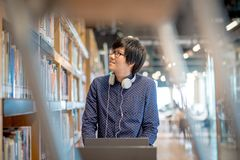 Giovane studente asiatico dell'uomo che sceglie libro in biblioteca Fotografia Stock Libera da Diritti