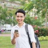 Giovane studente asiatico felice che per mezzo del telefono cellulare Fotografie Stock Libere da Diritti