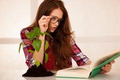 Giovane studente attraente di botanica con seedlnng ed i libri Immagini Stock