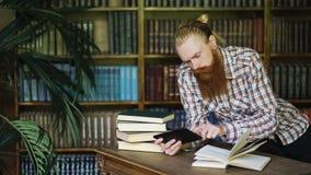Giovane studente barbuto in biblioteca che legge un libro e che per mezzo del computer della compressa per preparare per gli esam Fotografia Stock Libera da Diritti