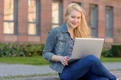 Giovane studente biondo che si siede su un banco e che lavora al suo computer portatile Fotografia Stock Libera da Diritti