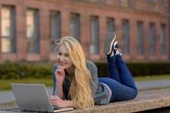 Giovane studente biondo che si trova su un banco e che lavora al suo computer portatile Immagini Stock