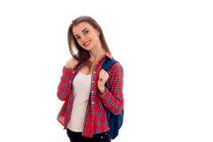 Giovane studente castana allegro con lo zaino blu sulle sue spalle che sorride sulla macchina fotografica isolata su fondo bianco Fotografia Stock Libera da Diritti