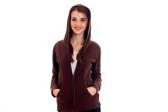 Giovane studente castana di Cutie in vestiti marroni di sport con il cappuccio che posa e che sorride isolato su fondo bianco Fotografia Stock