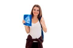 Giovane studente castana divertente con lo zaino ed i libri in sue mani che posano sulla macchina fotografica isolata su fondo bi Fotografie Stock Libere da Diritti