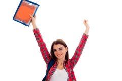 Giovane studente castana felice con lo zaino blu sulle sue spalle e cartella per i taccuini in sue mani che sorridono sulla macch Fotografia Stock