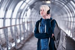 Giovane studente che ascolta la musica in grandi cuffie nel sottopassaggio Immagini Stock