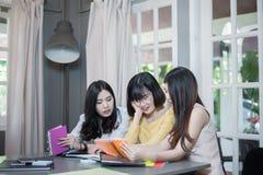 Giovane studente che discute le cose e che lavora con il labtop o taccuino su un progetto mentre sedendosi nel negozio di cofee Immagini Stock Libere da Diritti