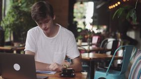 Giovane studente che fa compito in caffè, free lance che per mezzo della matita per attingere carta, posto di lavoro moderno che  archivi video