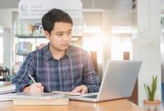 Giovane studente che lavora con il taccuino del computer Immagine Stock Libera da Diritti