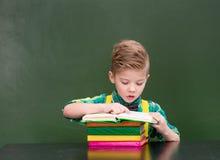 Giovane studente che legge un libro vicino alla lavagna verde vuota Immagini Stock