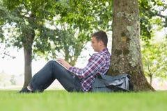 Giovane studente che per mezzo del suo computer portatile per studiare fuori Fotografia Stock