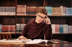Giovane studente che prepara per l'esame in biblioteca Fotografie Stock Libere da Diritti