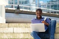 Giovane studente che si siede all'aperto e che per mezzo del computer portatile Fotografie Stock Libere da Diritti