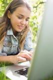 Giovane studente che si trova sull'erba facendo uso del suo computer portatile Immagine Stock Libera da Diritti