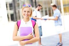 Giovane studente che sta e che sorride nella città universitaria Fotografia Stock