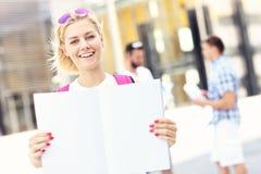 Giovane studente che sta nella città universitaria con un taccuino aperto Immagine Stock