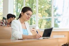 Giovane studente che studia nell'università che lavora con il computer portatile Fotografie Stock Libere da Diritti