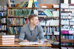 Giovane studente con il libro aperto che lavora in una biblioteca Immagini Stock