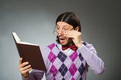 Giovane studente con il libro nell'apprendimento del concetto Fotografie Stock
