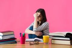 Giovane studente con l'espressione disperata che si siede al suo scrittorio Immagini Stock Libere da Diritti